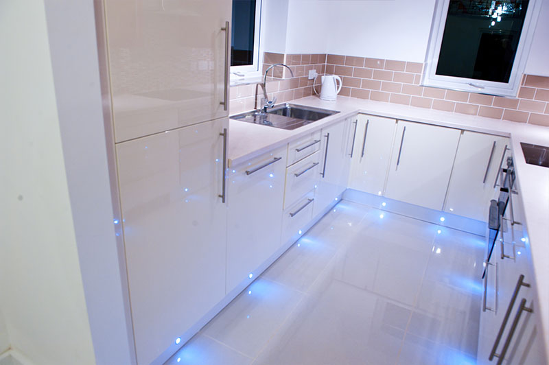 A new-build, modern kitchen with spotlights and floor lighting.